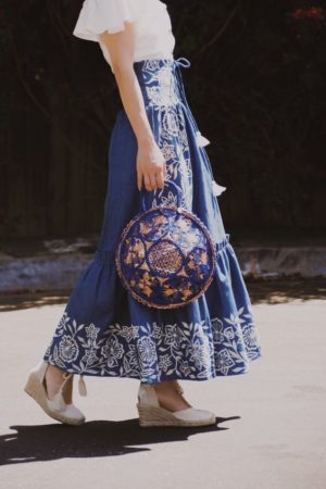 126ebdf03de75 Don't you just love summer embroidery? A blue embroidered maxi skirt paired  with a white peasant top and a round blue wicker bag is perfect for any  summer ...